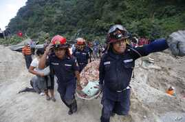 Rescue workers carry a body away from the site of a landslide in Santa Catarina Pinula, on the outskirts of Guatemala City, Oct. 2, 2015.