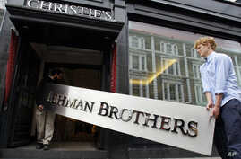 The Lehman Brothers corporate sign in polished metal is taken into an auction house in London, Friday, Sept. 24, 2010.