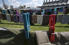 Lines of women's clothing hang, as a part of an art installation called 'Thinking of You,' by Kosovo born artist Alketa Xhafa Mripa, in Pristina stadium, Kosovo, June 10, 2015.