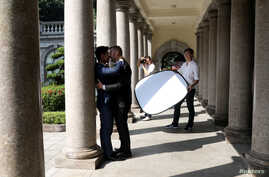 Lin Chinxuan, right, holds a reflector as Austin Haung, 32, photographs Kao Shaochun, left, and John Sugden during their pre-wedding photoshoot in Taipei, Taiwan, Nov. 11, 2018. Lin Chinxuan and Austin Haung are a couple and together they run Hiwow s