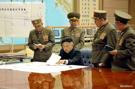 North Korean leader Kim Jong-un (C) presides over an urgent operation meeting on the Korean People's Army Strategic Rocket Force's performance of duty for firepower strike at the Supreme Command in Pyongyang, early March 29, 2013