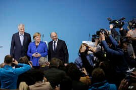 German Chancellor Angela Merkel is flanked by Bavarian governor Horst Seehofer (L) and Social Democratic Party Chairman Martin Schulz as they pose for a photo after the exploratory talks between Merkel's Christian Democratic block and the Social Demo