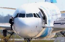 A man, leaves the hijacked aircraft of Egyptair from the pilot's window after landing at Larnaca airport, March 29, 2016.