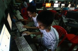 In this Sept. 27, 2012 photo, two Vietnamese students use Facebook at an internet cafe near their dormitory while they could not log in Facebook from their mobile phones because of firewall in Hanoi, Vietnam. In Vietnam, new blogs, Facebook accounts
