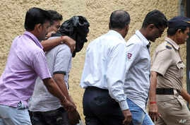 olice officials escort an accused, head covered with black cloth, in the gang rape of a young photojournalist in the Indian financial hub of Mumbai, Aug. 24, 2013.