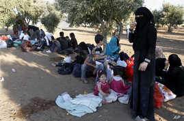 Newly-arrived Syrian refugee families rest after having crossed the border from Tal Shehab in Syria, through the Al Yarmouk River valley, to near Ramtha, Jordan, Sept. 15, 2012.