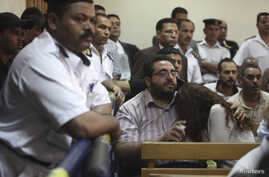 Friends of Egyptian suspects react as they listen to the judge's verdict at a court room during a case against foreign non-governmental organizations (NGOs) in Cairo, June 4, 2013
