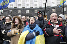 Supporters of Ukrainian EU integration sing and wave flags during a protest in front of the Ukrainian cabinet of ministers building in Kiev December 6, 2013. Ukrainian pro-Europe demonstrators vowed to stay on the streets and continue their blockade