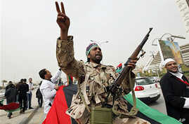 An armed Libyan rebel chant anti- Gadhafi slogans during a demonstration for students of the faculty of medicine of the University of Qar Younis, Benghazi, March 13, 2011