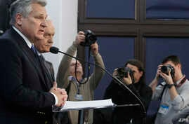 Former Polish President Aleskander Kwasniewski, left, and former Prime Minister Leszek Miller, second left, who were in power when the CIA ran a secret prison in Poland, speak to reporters in Warsaw about a report on CIA techniques, Dec. 10, 2014.