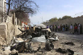 People look at the scene of a suicide attack next to the gate of the Presidential Palace in Mogadishu February 21, 2014. Al Qaeda-linked militants al Shabaab attacked the Somali presidential palace compound on Friday, blasting through a gate with a c