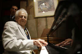 FILE - New York City's oldest cabaret singer and piano player, Irving Fields, plays the piano during a 100th birthday celebration for him at Nino's Tuscany restaurant, Aug. 7, 2015.