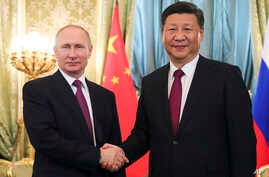 Russian President Vladimir Putin, left, shakes hands with the Chinese President Xi Jinping during a meeting in the Kremlin, in Moscow, Russia, July 4, 2017.