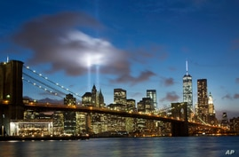The Tribute in Light rises behind the Brooklyn Bridge and buildings adjacent to the World Trade Center complex, Sept. 10, 2014 in New York.