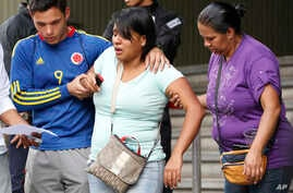Barbara Barca, a survivor of the stampede at a crowded nightclub, is helped by relatives as they leave police headquarters in Caracas, Venezuela, June 16, 2018.