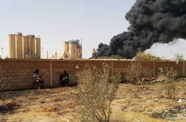 FILE - Members of forces loyal to Libya's eastern government sit near a factory during clashes with the Shura Council of Libyan Revolutionaries, an alliance of former anti-Gaddafi rebels who have joined forces with Islamist group Ansar al-Sharia, in