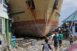 Men walk past Sabuk Nusantara, Oct. 4, 2018, which was swept ashore by the tsunami in Wani village on the outskirt of Palu, Central Sulawesi, Indonesia. The crew of the hulking ferry dropped by the tsunami in front of a row of houses in an Indonesian