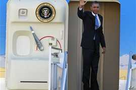 President Barack Obama waves as he boards Air Force One before departing the Orlando International Airport for Washington to monitor Hurricane Sandy, in Orlando, Florida, October 29, 2012.