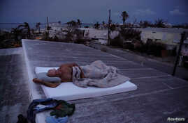 Matt Finn seeks a breeze as he lays down on the roof of his house that is still without power following Hurricane Irma in Big Pine Key, Florida, Sept. 25, 2017.