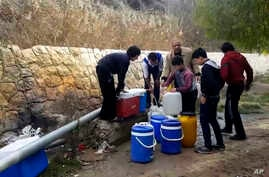 This frame grab from video provided By Yomyat Kzefeh Hawen Fi Dimashq (Diary of a Mortar Shell in Damascus), a Damascus-based media outlet that is consistent with independent AP reporting, shows Syrian residents filling up buckets and gallons of spri
