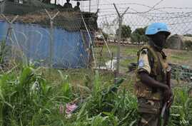 A U.N. peacekeeper stands guard at the U.N. Mission in South Sudan (UNMISS) base in Malakal, where some 19,000 people have been sheltering for nearly half a year.