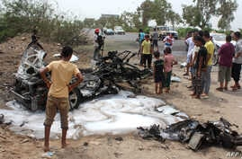 Yemenis inspect a charred vehicle following a suicide car bombing that targeted the convoy of Aden's governor, in the southern city of Aden on July 15, 2016.