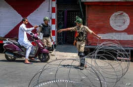 Indian paramilitary soldiers question a person on a scooter before letting him pass at a barbed-wire road checkpoint set up by Indian security forces in Srinagar, Indian-controlled Kashmir, July 7, 2017.