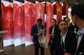 Attendees stand near a display of the Chinese flag during the China International Import Expo in Shanghai, Nov. 6, 2018.