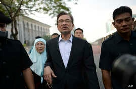 Malaysian opposition leader Anwar Ibrahim, center, walks with his wife Wan Azizah as they arrive for his final hearing of his sodomy conviction in Putrajaya, Malaysia, Tuesday, Oct. 28, 2014.
