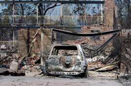 A burnt out car sits at the front of a house destroyed by bushfires in Winmalee in Sydney's Blue Mountains on October 18, 2013.