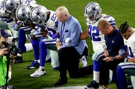 The Dallas Cowboys, led by owner Jerry Jones, center, take a knee during the national anthem prior to an NFL football game against the Arizona Cardinals, in Glendale, Arizona, Sept. 25, 2017.
