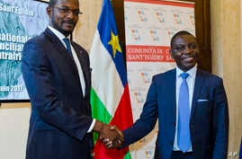 CAR Foreign Minister Charles Armel Doubane, right, and Armel Mingatoloum Sayo, head of the Revolution and Justice militia, shake hands after signing a Central African Republic peace accord at the Sant'Egidio headquarters in Rome, June 19, 2017. Membe