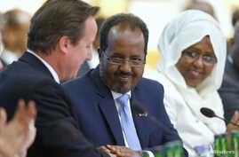 Britain's Prime Minister David Cameron (L) and Somali President Hassan Sheikh Mohamud (C) shake hands after making their opening speeches the Somalia conference in London May 7, 2013.