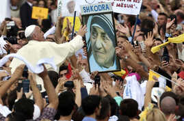 Pope Francis reaches for a poster of Mother Teresa as he is driven through the crowd, in Tirana, Sunday, Sept. 21, 2014.