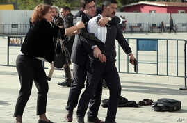 Dilek Dundar, journalist Can Dundar's wife, and his lawyer, second left, overpower a gunman just after the attack on Can Dundar outside city's main courthouse in Istanbul, May 6, 2016.