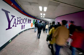 FILE - Chinese subway riders walk past a Yahoo advertisement at a metro station in Beijing.