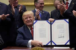 President Donald Trump hold up the Veterans Choice Program Extension and Improvement Act that he signed, April 19, 2017, in the Roosevelt Room of the White House in Washington.
