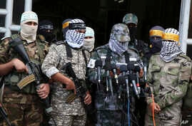 FILE - Masked Palestinian militants from Al Aqsa Martyrs' Brigade, a militia linked to the Fatah movement, give a press conference to condemn the decision by U.S. President Donald Trump to recognize Jerusalem as Israel's capital, in Gaza City, Dec. 7