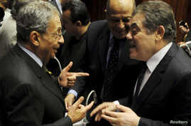 Amr Moussa (L), head of the assembly writing Egypt's new constitution, speaks with El-Sayed El-Badawi (R), the head of the Wafd party, before a vote at the Shura Council in Cairo, Dec. 1, 2013.
