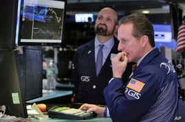 Specialists Glenn Carell (R), and James Denaro work on the floor of the New York Stock Exchange, March 27, 2017. Banks and industrial companies are leading stocks lower on Wall Street in early trading.