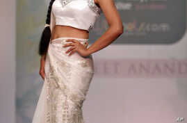 FILE - Bollywood actress Tanushree Datta presents a creation by designer Sanjeet Anand at the Bangalore Fashion Week in Bangalore, India, July 24, 2010.