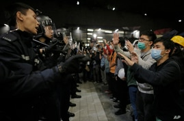 Police officers tell the protesters not to push after the protesters tried to break into the Legislative Council in Hong Kong Wednesday, Nov. 19, 2014.