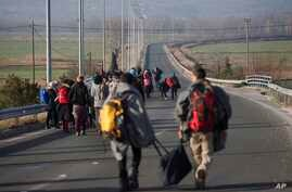 Refugees and migrants make their way to reach the borderline to Macedonia, near the northern Greek village of Idomeni, on Tuesday, Feb. 23, 2016.