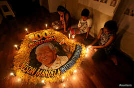 Children light candles beside a painting commemorating the 100th anniversary of South African revolutionary Nelson Mandela's birth at an art school in Mumbai, India, July 18, 2018.