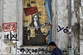A man walks past a political graffiti in central Athens by artist Bleeps reading' Bid! a few items left on sale' on May 4, 2017 one day after Greece and its creditors closed a troubled chapter on fiscal reforms with a preliminary deal on pension and