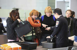 FILE - Travelers, left, and an official, right, argue at a security check at Hongqiao Airport's second terminal in Shanghai, China.