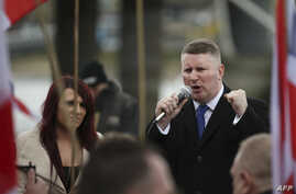FILE - Paul Golding (R) and Jayda Fransen (L), leaders of the far-right organisation Britain First talk during a march in central London on April 1, 2017.