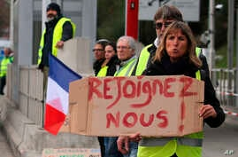 """A demonstrator holds a placard reading """"Join us"""" as protesters stand by toll gates on a motorway at Biarritz southwestern France, Dec. 5, 2018."""