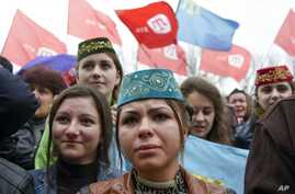 Crimean Tatars hold ATR TV station flags during a support rally in Simferopol, Crimea, March 31, 2015.