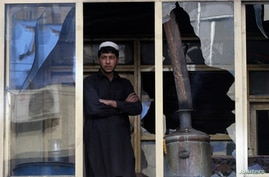 An Afghan man looks out from a window at the site of a suicide car bomb attack in Jalalabad province, March 20, 2014. Taliban fighters killed at least 11 people and wounded 22 in a suicide bomb attack and gunbattle at a police station in Afghanistan'